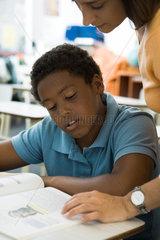 Teacher helping elementary school student with classwork
