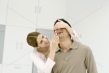 Woman covering man's eyes with her hand  feeding him a fresh strawberry