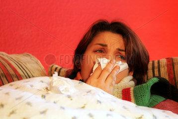 Eine Frau  liegt erkaeltet im Bett und putzt sich die Nase