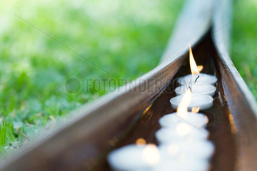 Lit votive candles floating in water in palm leaf