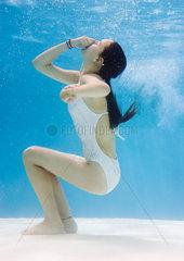 Teenage girl in pool  holding nose  underwater view