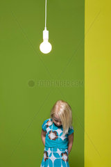 Little girl with hands behind back contemplatively looking down  illuminated light bulb suspended overhead