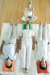 Alternative therapy session  three adults lying side by side while therapist puts hands out over man's head