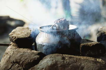 Tea steeping in cup placed atop cast iron pot cooking on traditional stove
