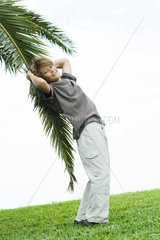 Boy leaning against palm branch  smiling at camera