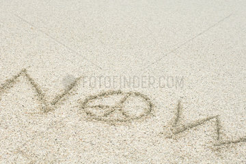 The word now written with a peace sign in sand (peace now)