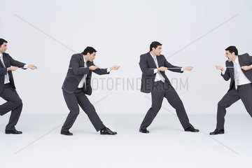 Businessman playing tug-of-war with clones of self  digital composite