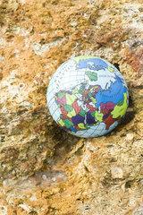 Globe nestled in rock