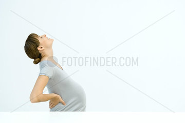 Pregnant woman holding back  leaning back  gritting teeth
