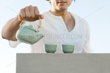 Man holding teapot  cropped  mid section