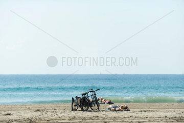Sunbathers and bicycles on beach