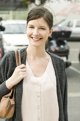 Woman walking in parking lot  smiling cheerfully