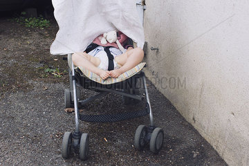Baby napping in stroller with face covered by blanket