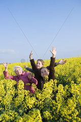 Senior woman and two granddaughters standing in field of canola in bloom  striking poses