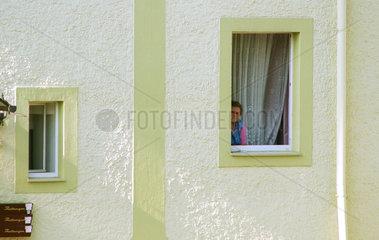 Eine Rentnerin linst aus dem Fenster (in Sachsen)