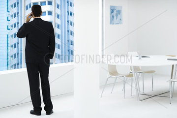 Businessman standing  looking out window  using cell phone