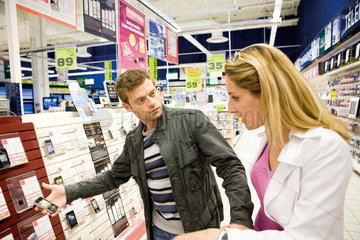 Couple looking at cell phones in electronics section of department store