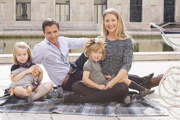 Family sitting on blanket in urban park  portrait