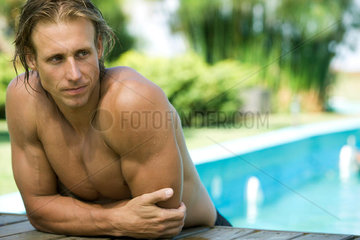 Muscular swimmer resting at edge of pool  leaning on elbow looking away
