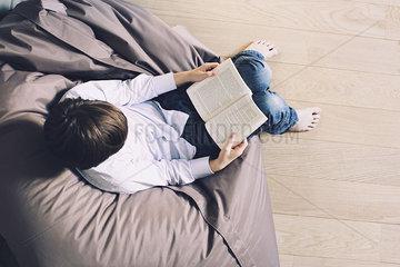 Boy sitting on beanbag chair  reading book