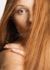 Woman with red hair covering half of face  hand on shoulder  portrait