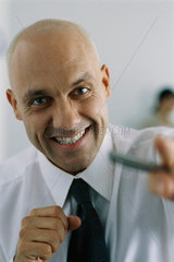 Businessman clenching fists  smiling at camera