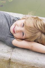 Little girl lying beside pond  portrait
