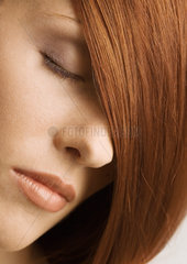 Woman's face and red hair covering one eye