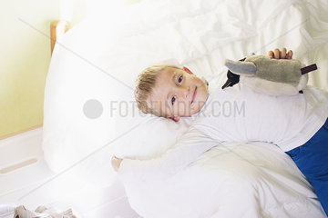 Boy lying on bed with stuffed penguin