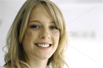 Blonde teenage girl smiling at camera  portrait
