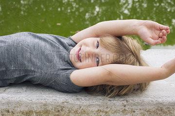 Little girl lying beside pond  smiling  portrait