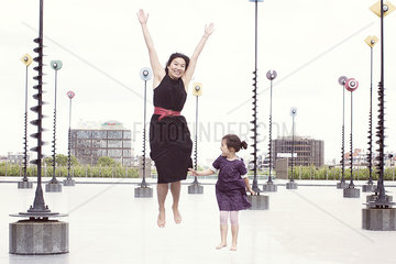 Mother and daughter jumping in front of whimiscal sculptures  La Defense  Paris  France