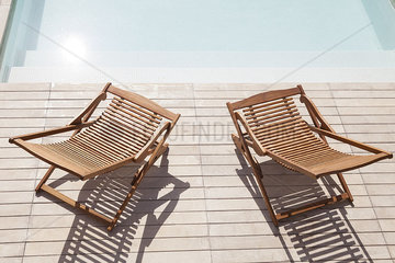 Wooden deck chairs beside pool