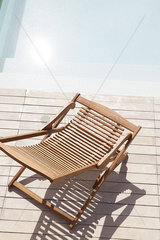 Wooden deckchair beside pool
