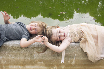 Young sisters lying down on beside pond holding hands