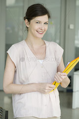 Woman carrying folders  smiling cheerfully  portrait