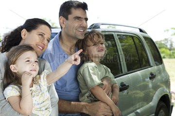 Family leaning against car  all looking as daughter points at something in distance