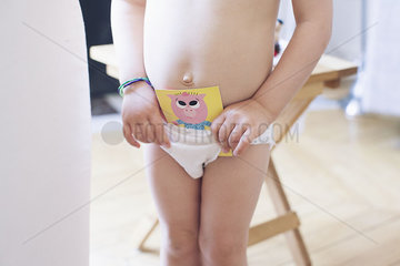 Toddler placing paper card in training underwear