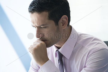 Businessman with hand under chin with look of concern
