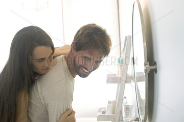 Woman embracing husband from behind