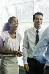 Business associates having lighthearted moment together in office