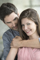 Woman smiling as husband embraces her  portrait