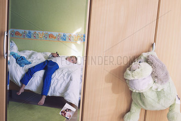Boy daydreaming on bed  reflected in bedroom mirror