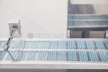 Pills on conveyor belt entering blisterpack sealing machine
