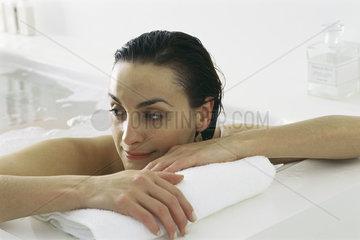 Woman in bath  leaning head against side of tub
