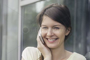 Woman using cell phone  smiling cheerfully