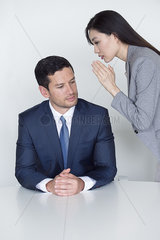 Assistant whispering in executive's ear