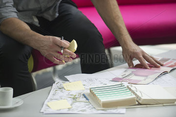 Man looking through catalog of color swatches