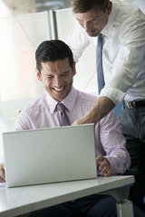 Office workers looking at computer together laughing