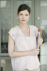 Woman carrying folders  smiling  portrait